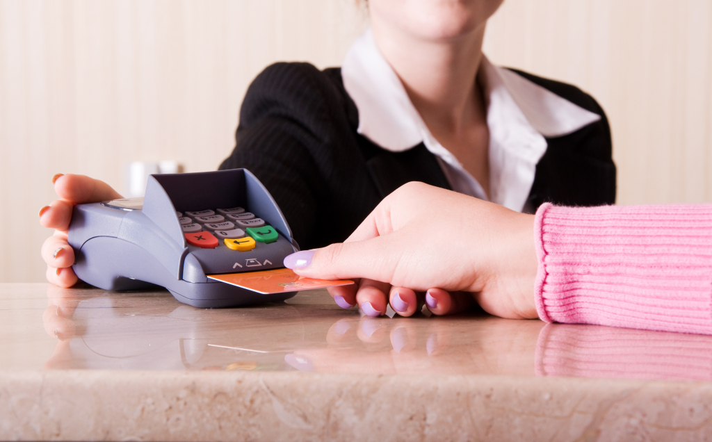 Close-up of woman hand holding credit card in payment terminal